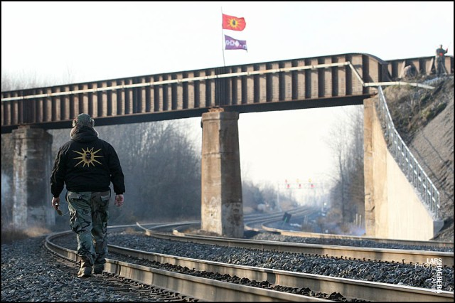 A Mohawks warrior walks beside the CN and the CP train tracks crossing in Tyendinaga, Ont., on Wednesday Jan. 16, 2013. Mohawk warriors block the trains tracks in support for the Idle No More movement during the National Day of Protest. THE CANADIAN PRESS/Lars Hagberg