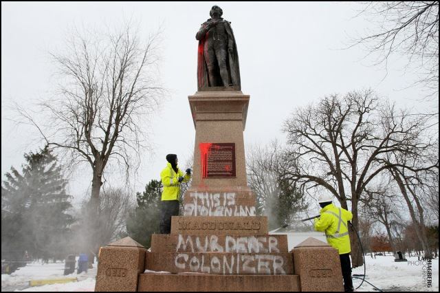 City of Kingston employees remove graffiti on the statue of Sir John A. MacDonald, Canada's first Prime Minister, in City Park in Kingston, Ont. on Friday Jan. 11, 2013. It's the former prime minister's 198 birthday today, with a celebration planned for noon.THE CANADIAN PRESS/ Lars Hagberg