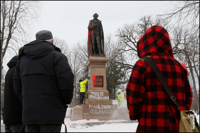 City of Kingston employees remove graffiti on the statue of Sir John A. MacDonald, Canada's first prime minister while some people look on, in City Park in Kingston, Ont. on Friday Jan. 11, 2013.  It's the former Prime Minister's 198 birthday today, with a celebration planned for noon. THE CANADIAN PRESS/Lars Hagberg