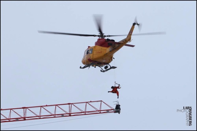 A rescue worker from a Canadian military helicopter retrieves a crane operator who was stranded atop a crane when fire broke out in an apartment building under construction in downtown Kingston, Ontario, Tuesday, Dec. 17, 2013. The crane operator was taken to a waiting ambulance, and police say he was believed to have only minor injuries. The Canadian Press, Lars Hagberg