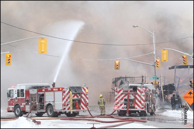 Firefighters battle a major fire in an apartment building that was under construction in downtown Kingston, Ontario, Tuesday, Dec. 17, 2013. A Canadian military helicopter rescued a man who was trapped on top of a construction crane because of the massive fire. The Canadian Press, Lars Hagberg