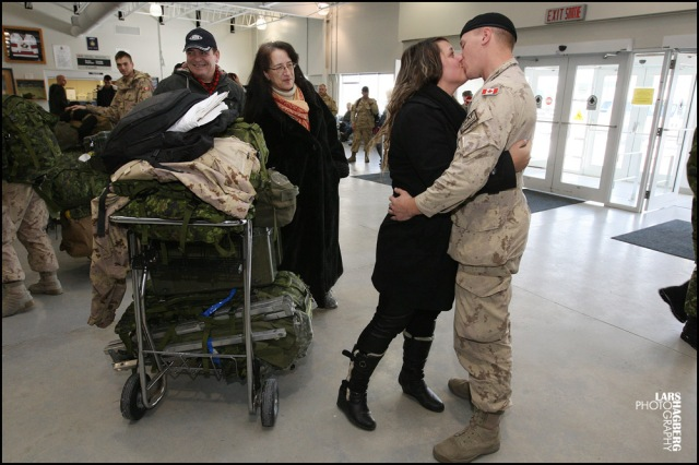 Cpl. Anthony Jacques kisses his girlfriend, Catherine Berthiaume, from Montreal, Que., while Anthony's mum Lin and dad Daniel, looks on, at the arrival gate at CFB Trenton in Trenton, Ont., on Thursday on Jan. 23, 2014. Around hundred Canadian troops returned from serving several months in Afghanistan. Lars Hagberg for the Globe and Mail