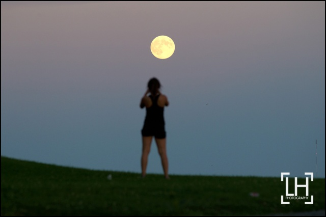 Lindsay Meier takes a picture of the full moon as it rises over Lake Ontario in Kingston, Ont., on Monday Sept. 8, 2014. This in the third super moon this lunar calendar. Lars Hagberg/THE CANADIAN PRESS