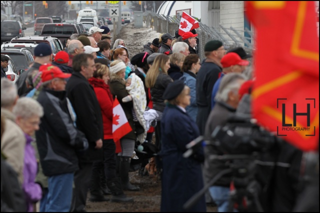 People stand at the fence at CFB Trenton as the body of Sgt. Andrew Joseph Doiron arrive at Canadian Forces Base Trenton in Trenton, Ont., on Tuesday March 10, 2015. Sgt. Doiron was killed by friendly fire during operation Impact on March 6, in northern Iraq. Doiron was a member of Canadian Special Operations Regiment, based at Garrison Petawawa, Ontario. Doiron's death is the first casualty for Canada during the mission in Iraq.  Lars Hagberg/THE CANADIAN PRESS