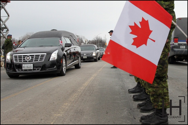 People wave Canadian flags as the hearse carrying the body of Sgt. Andrew Joseph Doiron leaves Canadian Forces Base Trenton in Trenton, Ont., on Tuesday March 10, 2015. Sgt. Doiron was killed by friendly fire during operation Impact on March 6 in northern Iraq. Doiron was a member of Canadian Special Operations Regiment, based at Garrison Petawawa, Ontario. Doiron's death is the first casualty for Canada during the mission in Iraq.  Lars Hagberg/THE CANADIAN PRESS